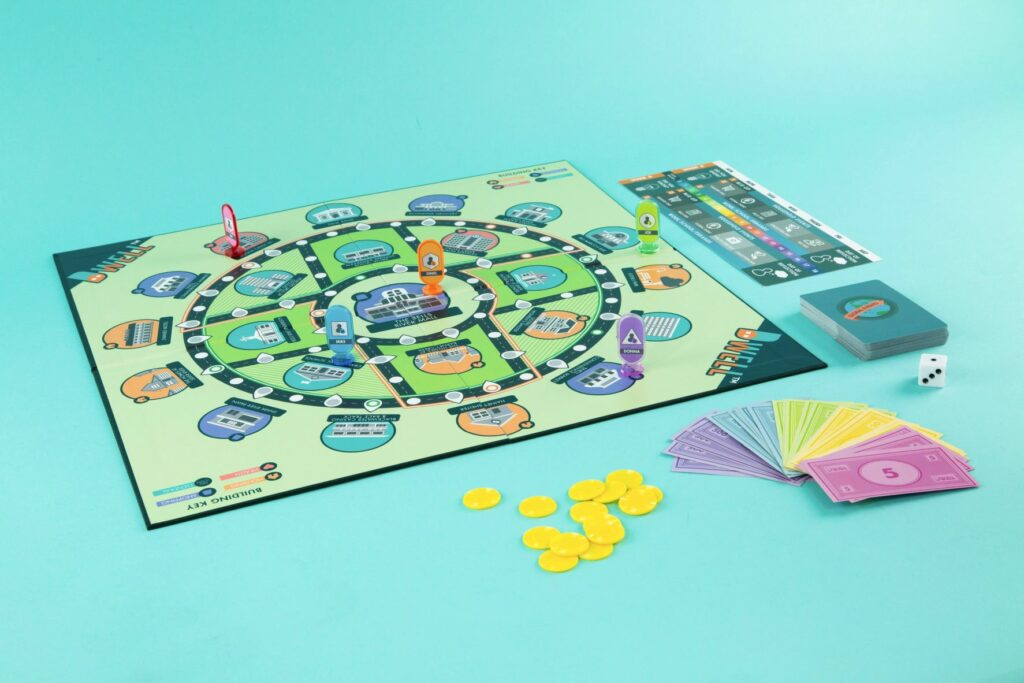Dwell tabletop simulation game set with board open and game components spread around and on the board.
